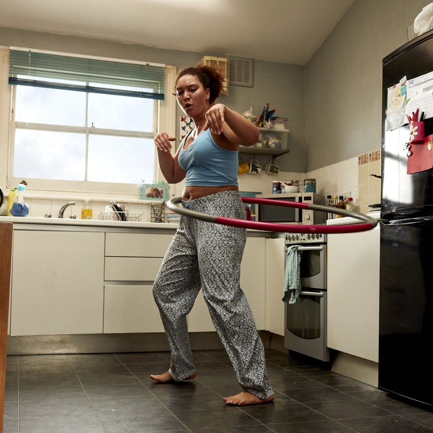 lady hula hooping in her kitchen